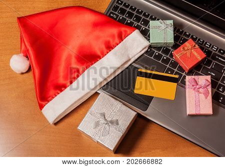 Laptop credit card gift boxes and santa hat top view on wooden background. Christmas online shopping concept.