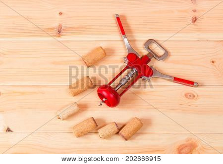Corkscrew for wine and corks on wooden background