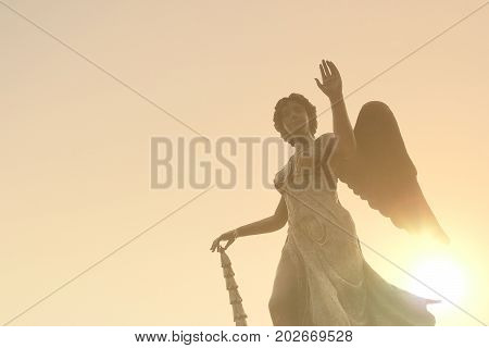 Beautiful angel statue in sunlight before sunset, faith and religion concept