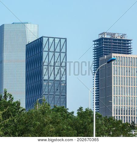 view of contemporary glass building with green trees,tianjin,china.