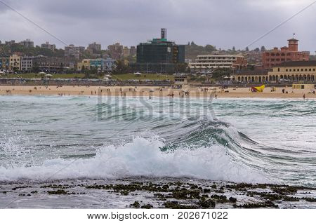 Ocean wave close up with people on the beach on the background. Bondi beach Australia. Selective focus shallow DOF