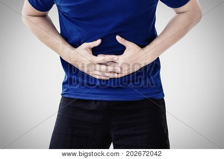 man holding his stomach in pain on grey background