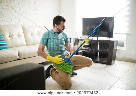 Attractive Man Using Broom As A Guitar
