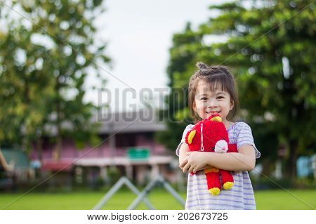 Cute girl hugging red doll with blurred background selective focus.