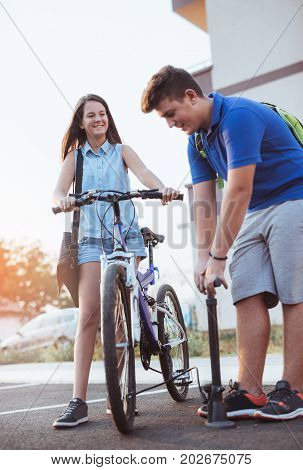 Teenager boy inflating bike tire to help his female friend outdoor summer photo