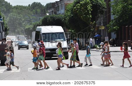 CHORTKIV - Ternopil - Ukraine - June 24 2016 A group of children at a crosswalk crossing the road. Before children convoy of vehicles.