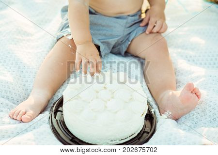 Baby boy eating with your hands white cake