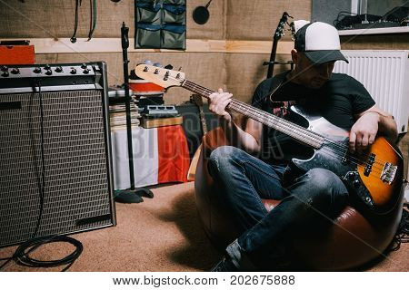 Bass guitarist playing guitar in music studio. Band repetition in garage before concert, musical background