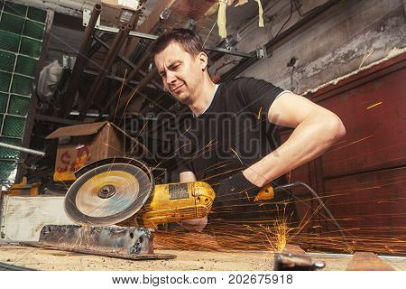 A strong dark-haired serious man builder in a black T-shirt saws a metal saw in a workshop with a circular saw around a lot of tools and equipment