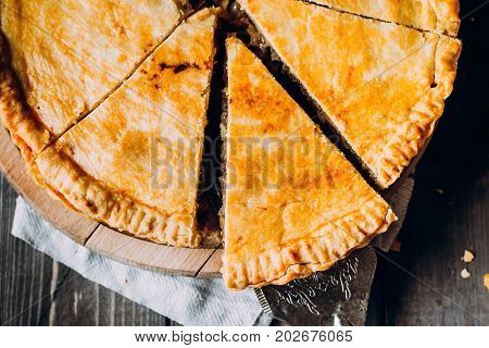 Fresh Meat pie on the wooden board on table background. Pie with cabbage and minced beef. Top view copy space