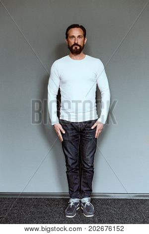 Full length portrait of mature man in casual clothes. Mid aged beardy actor posing on casting.
