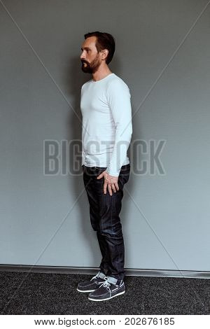 Side view of an actor standing on grey backdrop. Side view of man in full length posing for casting.