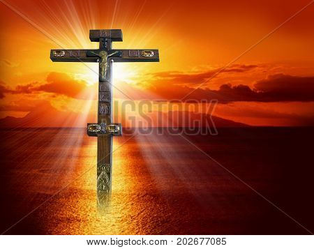 Silhouette of the crucified Jesus Christ on the cross against the red sky. The Biblical prophet is a symbol of death. Calvary Christmas Easter background.