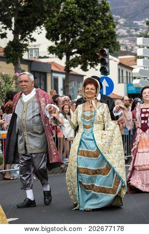 FUNCHAL MADEIRA PORTUGAL - SEPTEMBER 4 2016: Couple in historical fashion dress durnig historical and ethnographic parade of Madeira Wine Festival in Funchal. Madeira Portugal