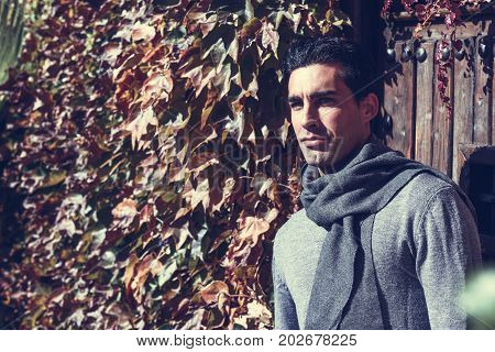 Handsome Man Wearing Winter Clothes In Wooden Background.
