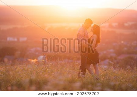 Man and girl lovers in love romantic date kissing, hugging sunset, sunrise against  background of mountains and fog, the sun, clouds in fiery red, orange colors. concept of wedding, first kiss, love, date. copyspace
