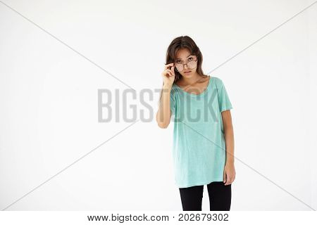 Isolated studio shot of perplexed beautiful young Latin woman with long loose natural hair wearing blue t-shirt and stylish eyeglasses peering at camera posing at white blank copyspace wall