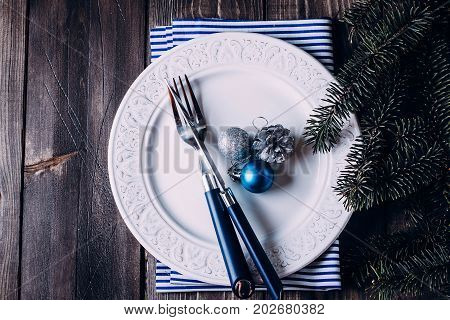 Christmas table setting. White plate knife and fork napkin. Silver and Blue Christmas Decorations fir branch candy cane on wooden background table. Top view.