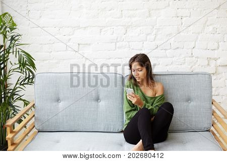 Modern teenage girl enjoying online communication at home. Cute young Latin female in casual clothes browsing internet in the morning reading world news and checking newsfeed via social networks