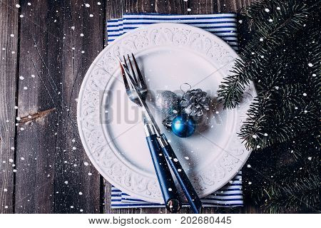 Christmas table setting. White plate knife and fork napkin. Silver and Blue Christmas Decorations fir branch candy cane on wooden background table. Top view. Xmas concept