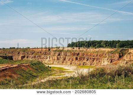 Open-cast quarry, limestone mining, orange sand and clay mountains and blue sky