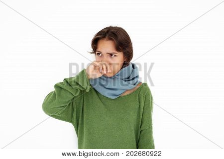 Healthcare unwellness disease illness and sickness concept. Uunhappy young brunette Latin woman having cold or flu trying to warm up wearing sweater and scarf covering nose while sneezing