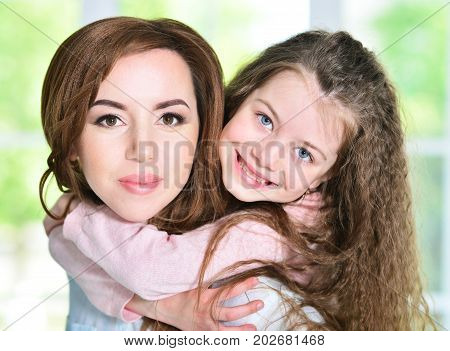 Close up portrait of cutelittle girl hugging mother