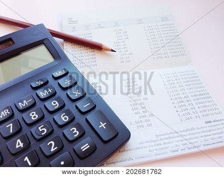 Business, finance, saving money, banking, loan, investment, taxes or accounting concept : Calculator, pencil and saving account book or financial statement on office desk table