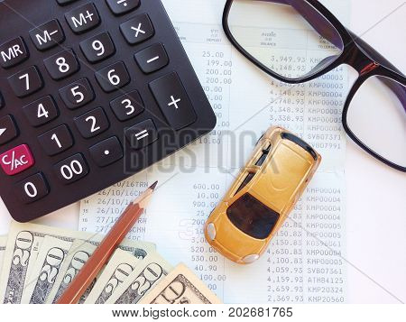 Business, finance, saving money, banking or car loan concept : Miniature car model, calculator, dollar money and saving account book or financial statement on office table