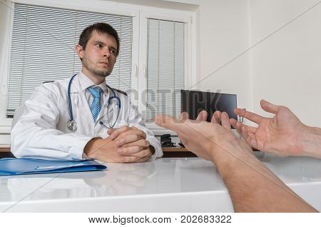 Practitioner Doctor Is Talking With Patient In Office. Medical C