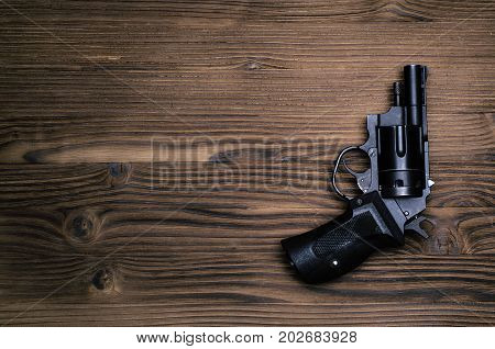 Gun revolver on wooden table background. Handgun on table surface.
