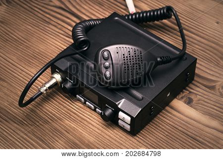 cb Radio transmitter isolated on wooden table background.