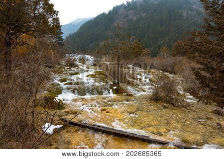Waterfall in the forest. Stream of water on the rocks. Clean and cold water over the coniferous forest. Stones in the snow. Powerful rocks and a stream of water