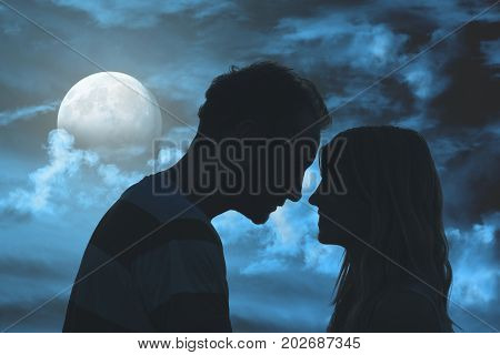 Silhouettes of a young couple under the moonlit sky.