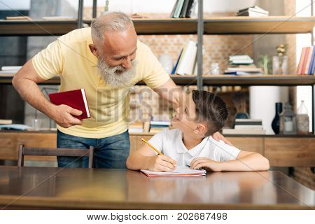 Doing fine. Pleasant senior man patting his beloved grandson on the shoulder and asking him about his progress in doing math home assignment
