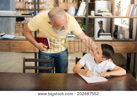 How are you. Caring loving grandfather bending over the table and asking his grandson about his progress in doing home assignment while they smiling at each other broadly