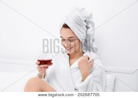 Beautiful young woman after shower in bathrobe with glass of red wine at home