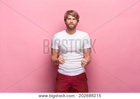 The anger and tense man at pink studio background as tv fan