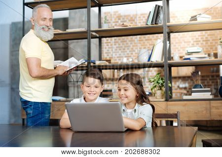Different interests. Adorable pre-teen brother and sister sitting at the table and watching a video while their grandfather reading a book