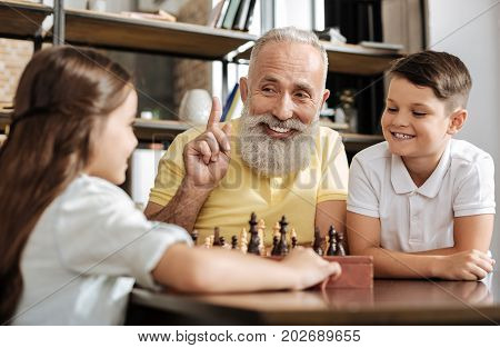 Smart idea. Cheerful senior man raising a finger, being happy to come up with a new idea for his next chess move when playing chess with his granddaughter and grandson