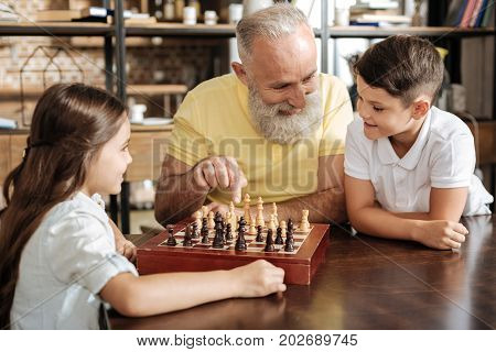 Helpful idea. Smiling senior man suggesting his beloved grandson the next possible move while the boy playing a chess game with his charming sister