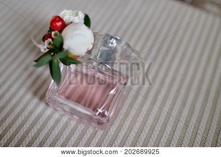 Beautiful bouquet and perfume bottle for bride and groom. Beauty of wedding accessories indoors. Close-up bridal bunch of florets and perfumery. Female and male decoration. Colorful flowers for woman