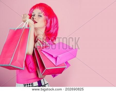 Girl wearing red wig and fashionable clothes. Woman with shopping bags. Holidays celebration concept. Sale and black friday. Fashion shopper posing on pink background copy space