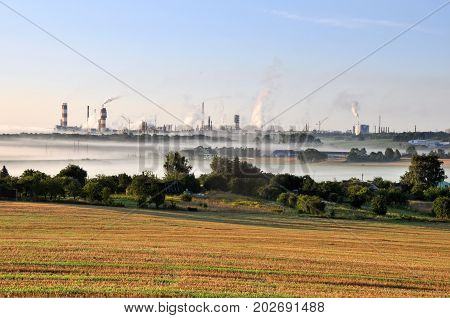 Working Nitrogen Plant in smoke in summer morning. Abandoned village in the foreground. Grodno, Belarus.