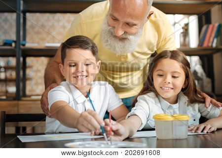 My beloved artists. Happy elderly man standing hugging his little grand-children from behind and watching them sit at the table and chose watercolors from the palette