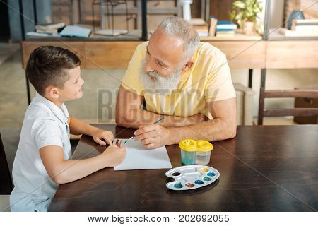 Creativity vibes. Happy pre-teen boy sitting at the table next to his grandfather and discussing with him their future watercolor picture