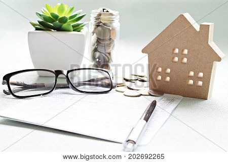 Business, finance, saving money, banking, property loan or mortgage concept :  Wood house model, saving account book or financial statement and coins on office desk table