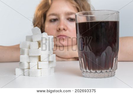 Diabetic woman is looking on glass with cola drink and heap of sugar. Unhealthy eating concept.