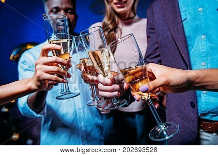 cropped shot of young multiethnic people clinking glasses of champagne at new year party