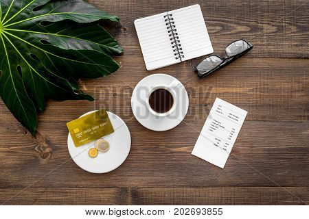 Pay restaurant bill. Bill, bank card, coins near cup of coffee on dark wooden table top view.